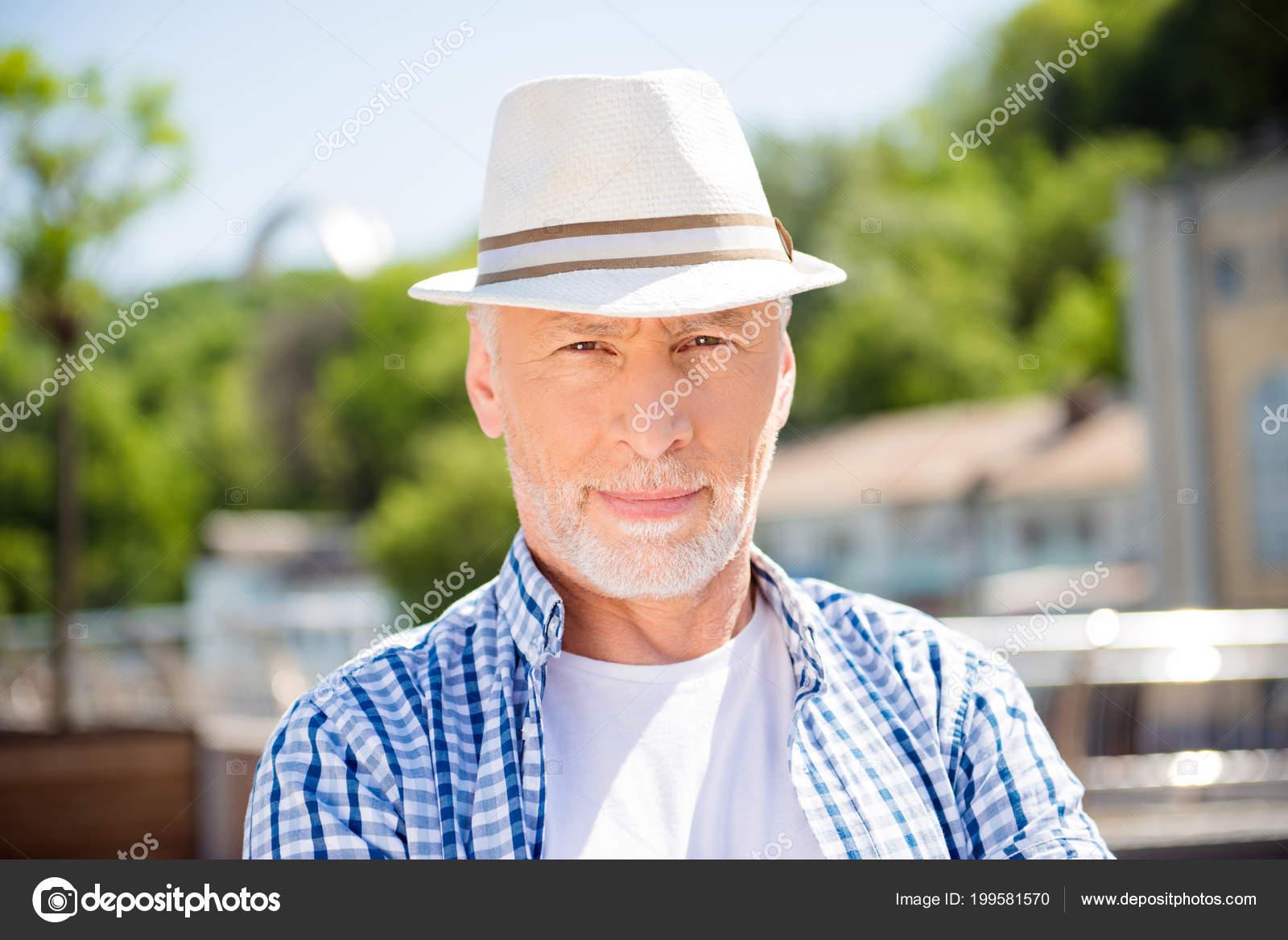 Testa colpo ritratto di uomo d affari concentrato attraente in cappello di  paglia sopra priorità bassa strada vaga che guarda l obbiettivo. 6d63b27259a3