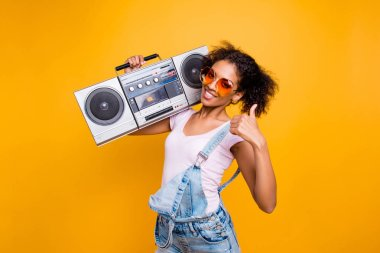 Yes, done! Portrait of trendy stylish girl in eyewear holding boom box on shoulder gesturing thumb up sign looking at camera isolated on yellow background. Recommend choice advice concept