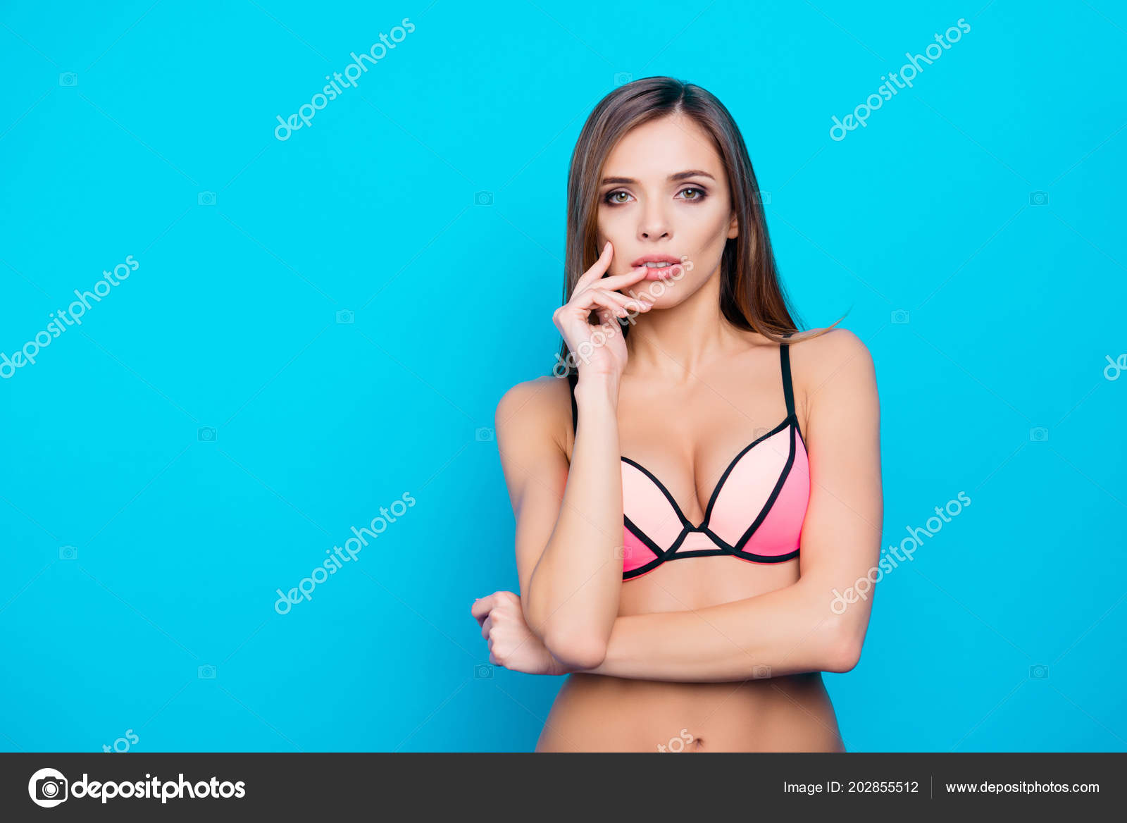 cbf0359f8b Portrait with copy space empty place of trendy stylish girl in swim wear  holding hand near mouth looking at camera standing over blue background with  ...