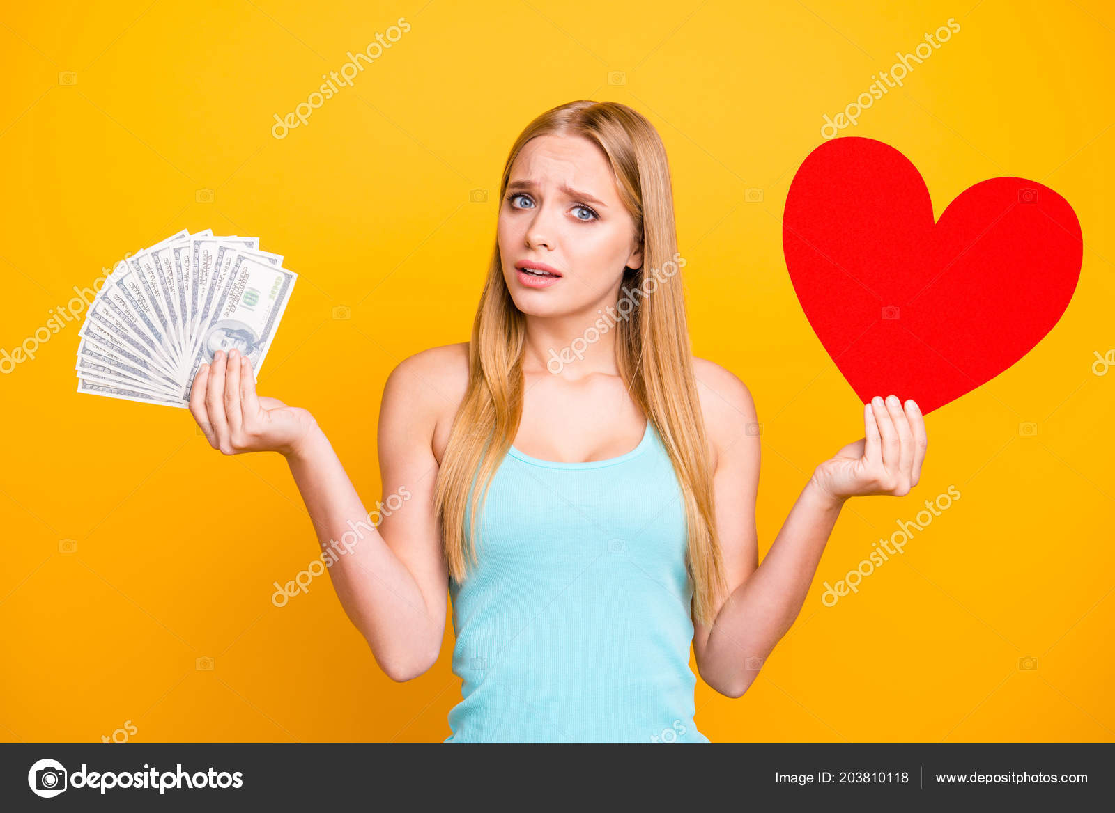 324c6f0ca898 Young beautiful girl isolated on yellow background looks at the camera and  hold money in one hand and big paper carton heart figure in other.