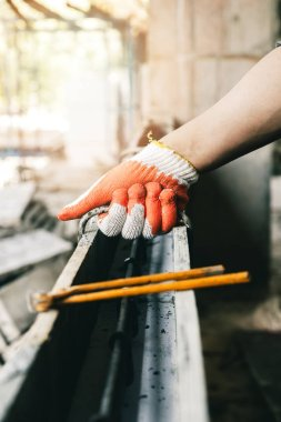 Close up of workers hands using pincers bind steel wire to rebar before concrete is poured over it.
