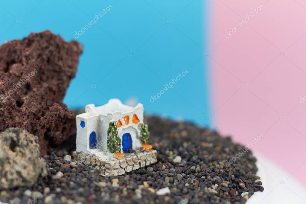 Animated model of a Greek house on a rock on a neon and pink background.