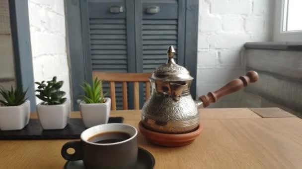 Detailní záběr na kávové konvice s přírodním kávou, šálek kávy na stole, káva k snídani, dobré ráno.