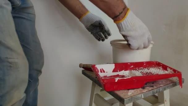 ein grauhaariger bärtiger Mann mischt weiße Farbe in einem Eimer mit einem Stock und gießt sie in den Behälter, Vorbereitung für das Streichen von Wänden in einem Raum.