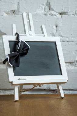 Close-up of a miniature chalk board and bow tie on a white brick wall background, selective focus
