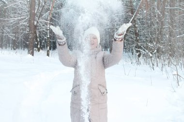 Young woman in winter clothes in a snowy forest throws white snow and laughs, selective focus