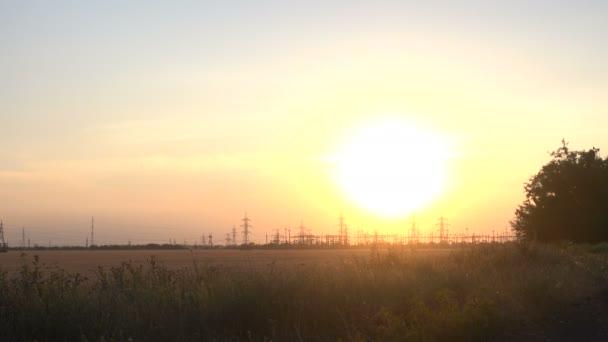 Vedení vysokého napětí při západu slunce. Poláci s dráty