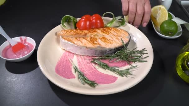 Salmon steak poured with lemon juice. Slow motion