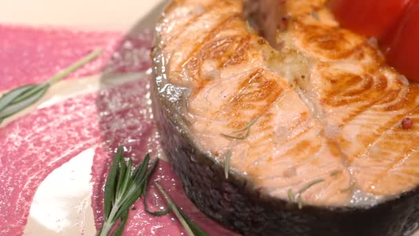 Salmon steak sprinkled with rosemary. Slow motion