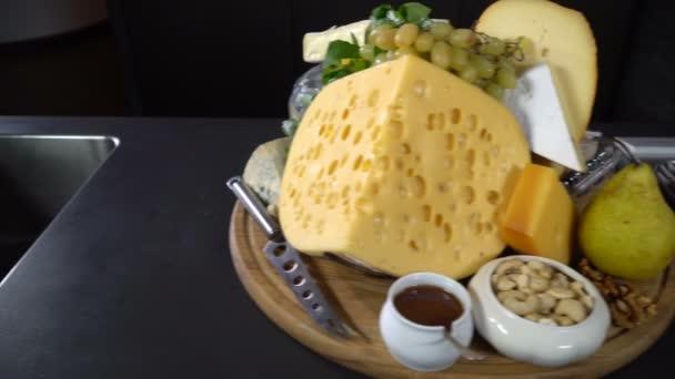 Druhy sýrů s ořechy a ovocem na stole