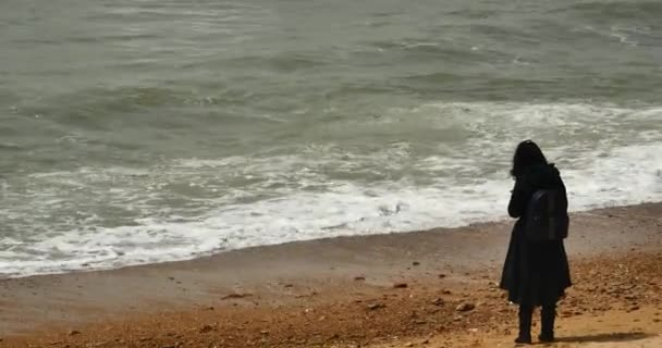 4k a woman is facing the sea,wide ocean surface,waves washed sand,Big waves and surge.