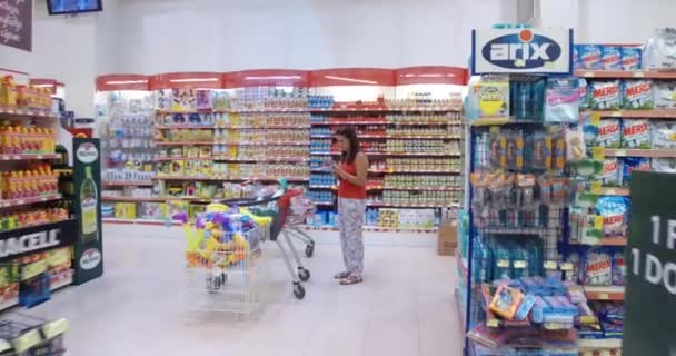 Žena nakupování v supermarketu. Sledovat záběr ze zadní strany mladá žena s košíkem v nákupním centru, pečlivě analyzovat produkty na trhu