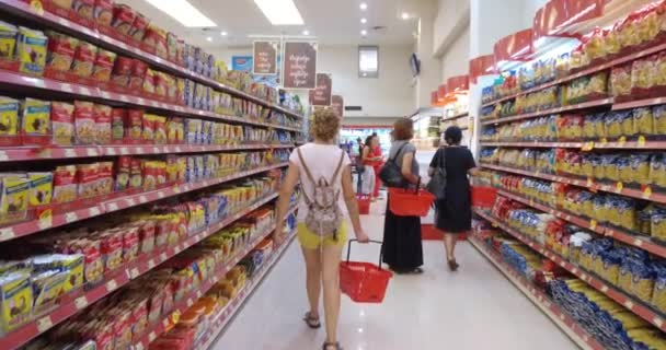 Woman is shopping at the supermarket. Follow shot from back of young woman with basket in shopping center, carefully analyzing products in a market.