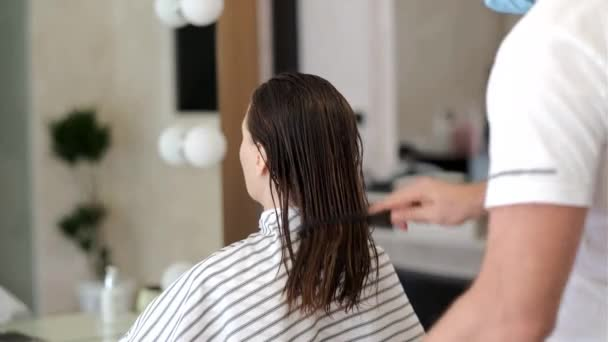In a beauty salon, a hairdresser combing the clients wet hair after washing her hair before cutting her hair