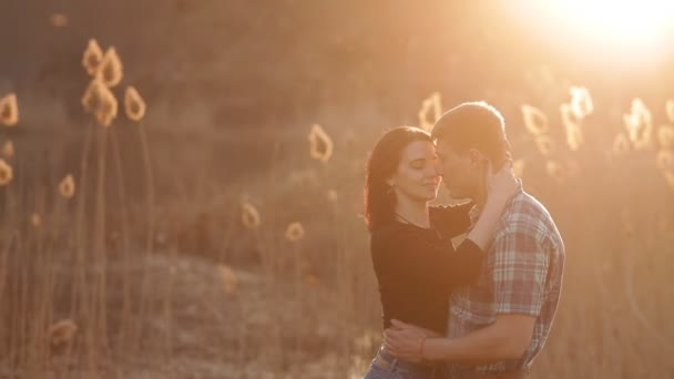 Loving couple hugs and kisses in a romantic setting during sunset