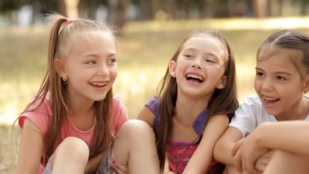 I bambini hanno un sacco di divertimento in estate sul prato nel parco, ridendo e chiacchierando allegramente. Risata del bambino.