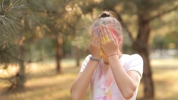 Ein Kind hat Spaß beim Spielen in der Natur mit bunten Farben und Sand. gießt er sich farbigen Sand ins Gesicht. Kinderfreuden. Kinderspiele