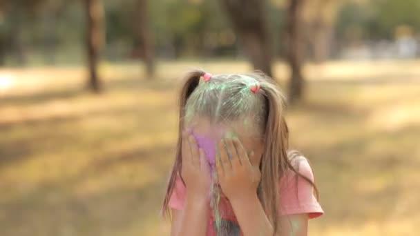 niedlichen kleinen Kind Spaß an der Natur spielen mit bunten Farben und Sand. gießt er sich farbigen Sand ins Gesicht. Kinderfreuden. Kinderspiele