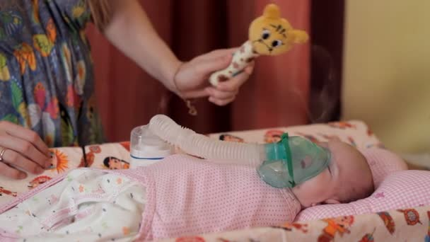 Young mother makes her baby inhalation with a special device
