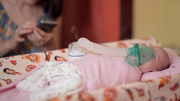 Lying on the bed, the baby is given an inhalation with an appropriate device, and his mother at this moment uses a smartphone