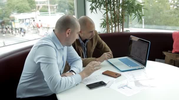Két üzleti férfi ül egy laptop, és üzleti fejlődésének nyomon követése. Üzleti