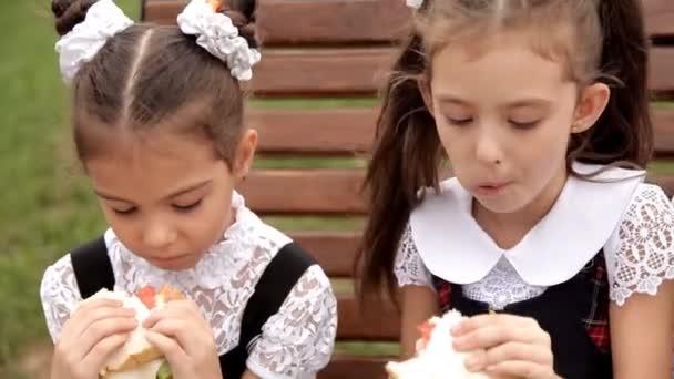 Děti ve školní uniformě, po třídy tráví čas v parku v dolní části sendvič, jíst sendviče a chat. Škola, potraviny, dovolená