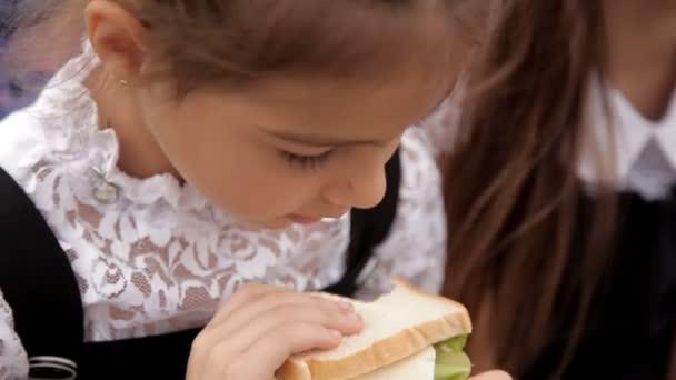 Děti ve školní uniformě po hodině sedí v parku a jíst sendviče s greeny. Výborné jídlo, zdravé jídlo