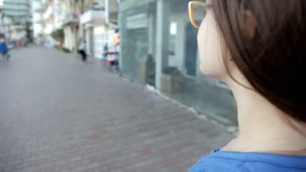Mladá dívka chodí přes město, ležící u moře. Odpočívat, chůze