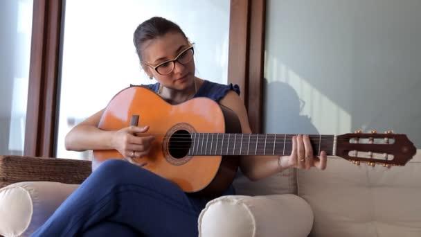 Mladá dívka sedí na gauči a hraje na kytaru
