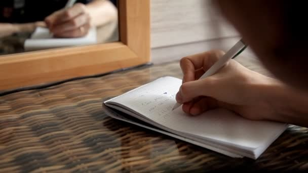 A young girl sits in front of a mirror takes notes in a notebook I love you and numbers