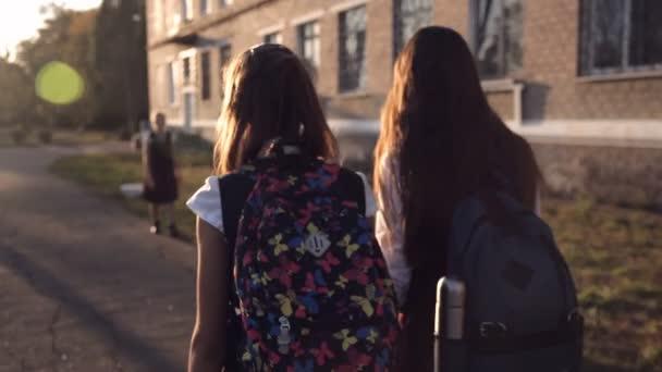 Két tini lányok az egyenruha jön vissza az iskolából haza, és séta az utcán, miközben beszélt. Vissza a véleményt. Hátsó