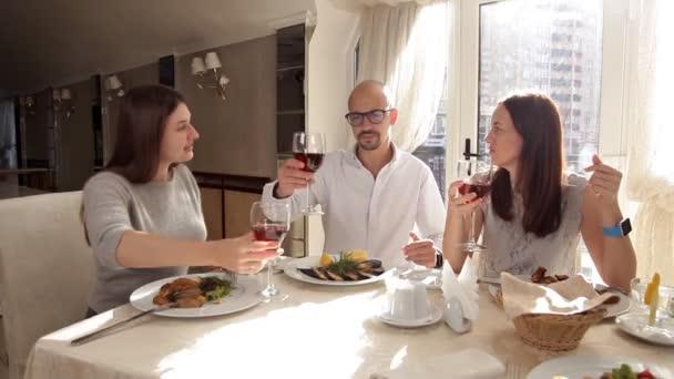 Přátelé mají večeři v restauraci a pití vína
