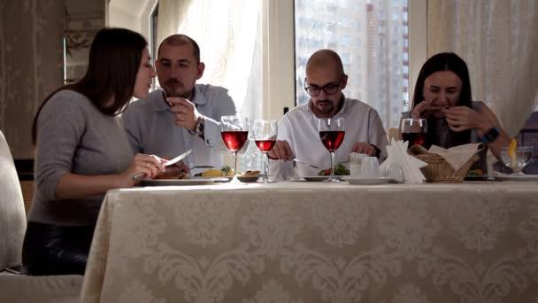 Skupina přátel se těší večeři s vínem v restauraci