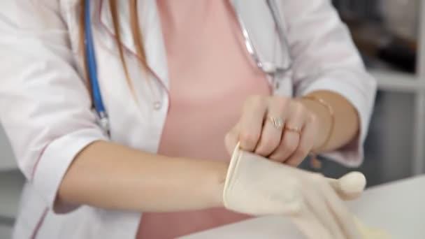 Hände tragen einen blauen Latex-Handschuh auf weißem Hintergrund