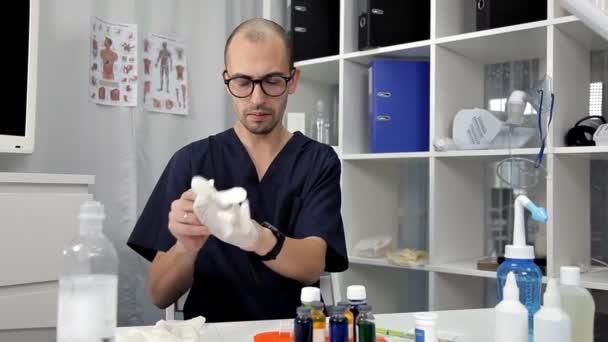 Arzt zieht blaue Latexhandschuhe an, Nahaufnahme. Arzt desinfiziert Hände