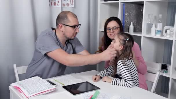 fürsorglicher Arzt untersucht ein kleines Mädchen im Büro