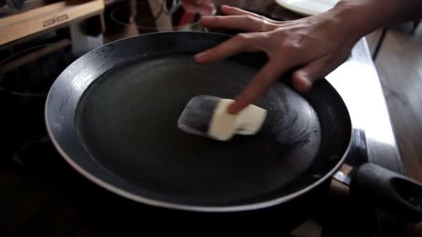 Dívka se šíří máslo na rozžhavenou pánev. Snídaně vaření