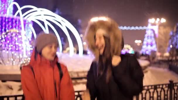 Mladé dívky chodit v zimě na hlavním náměstí města poblíž vánoční stromeček. Svátek, sníh, joy