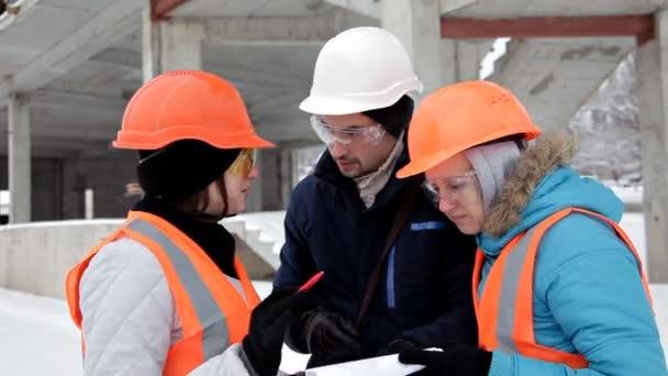 Dvě ženské inspektorů a architekti projednat s vedoucí inženýr o projektu výstavby