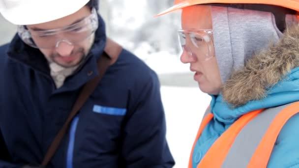 Stavební dělník a inženýr mluvil na staveništi. Dělníci v přilbách mimo budovu