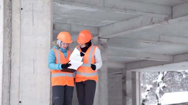 Construction worker and engineer talking on a construction site. Workers in helmets outside the building