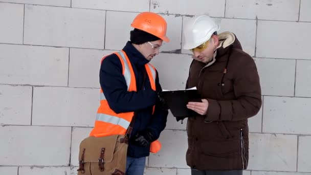 Mérnök és építész megvitat egy tervez tervez. Bukósisakot van a fején. Munka, projekt
