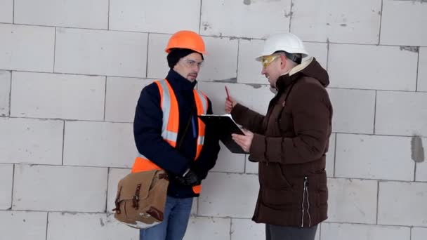 An engineer and architect discuss a project plan. They have a protective helmet on their head. Work, project