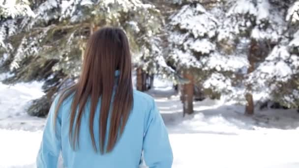 Beautiful woman walking among the snowy trees in the winter forest and enjoying the first snow