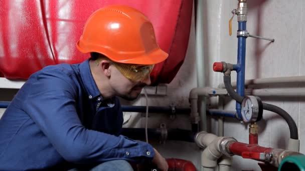Inženýr v dílech brýle v kotelně, kontroluje údržbu topného systému zařízení