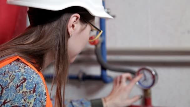 Ingenieurin überprüft die Daten der Heizungsanlage im Heizungsraum