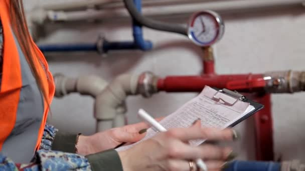 Samice technik kontroluje data topného systému zařízení v kotelně