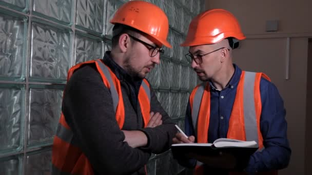 Two engineers discuss and make notes about the system check done