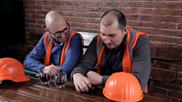 Two engineers sit at the table and drink coffee, chat, make notes
