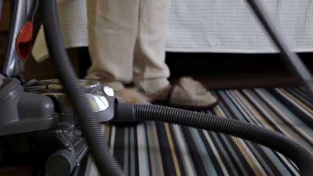 Mladá žena pomocí vysavače při čištění koberců v domě. Úklid domu